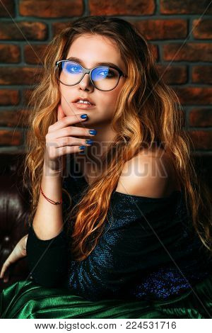Attractive blonde woman posing on a leather sofa in elegant spectacles. Beauty, fashion. Optics, eyewear.
