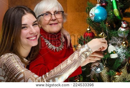 family at new year. senior grandma and young caucasian woman decorating christmas tree. old grandmother and granddaughter, teen, teenager. happy company. cheerful girl smiles, laugh. festive spirit