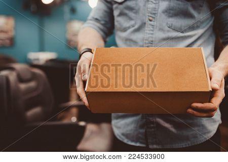 Barbershop. Barber keeps Mock-Up MockUp Cardboard Package box in shop. Ready For Your Design