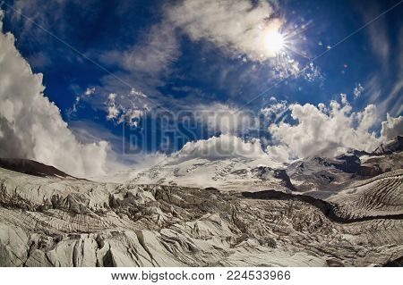 Sun and sunbeams high in the cloudy sky over the big icy mountain peak with cliff and glacier. View from high altitude