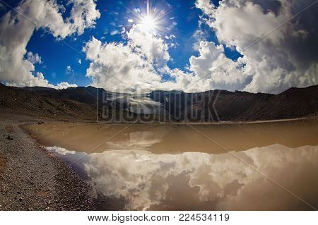 Sun and sunbeams high in the cloudy sky over the lake in the mountains with cliff and glacier. View from high altitude