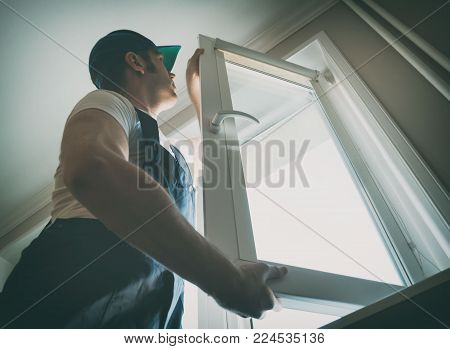 Professional handyman in uniform installing window at home.