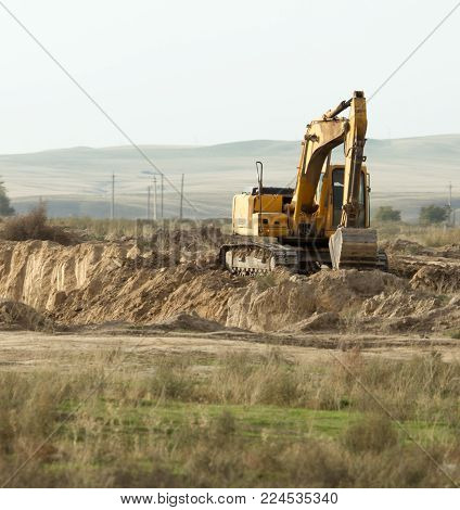 excavator digging a hole . In the park in nature