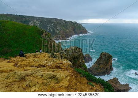 COLARES, PORTUGAL - DECEMBER 28, 2017: Coastal landscape in Cabo (Cape) da Roca, with visitors, Portugal. It is the westernmost point in mainland Europe