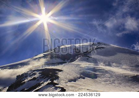 Sun and sunbeams high in the sky over the big icy mountain peak. View from high altitude