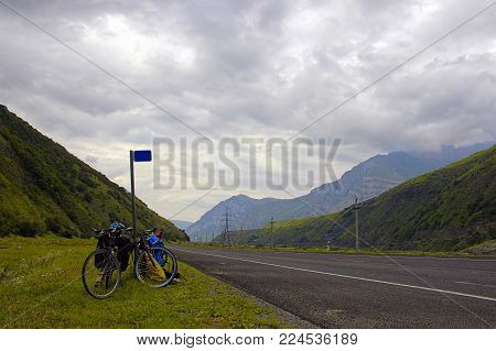 Highway running away through the mountain valley between high green ranges under cloudy sky. Two bicycle are standing near the signpost.