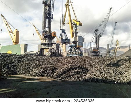 Heap of coal anthracite in the port. Port cranes for coal loading.
