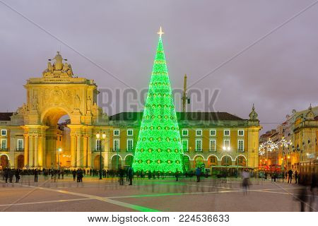 LISBON, PORTUGAL - DECEMBER 28, 2017: Sunset scene of the Terreiro do Paco, Commerce square, with Arco da Rua Augusta, a Christmas tree, locals and visitors, in Lisbon, Portugal