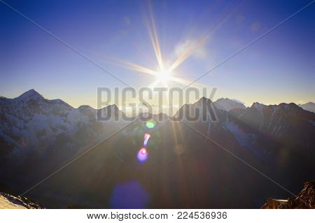 Beautiful sunset with sunbeams in the mountains view from a high altitude. Clear sky. High icy peaks.