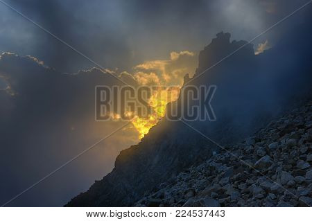 Golden cloudy sunset in the mountains with cliff. View from high altitude.