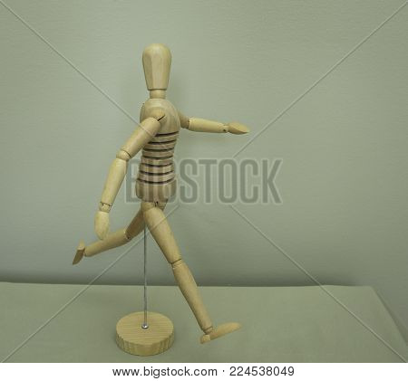 Wooden art mannequin in running pose, arms outstretched