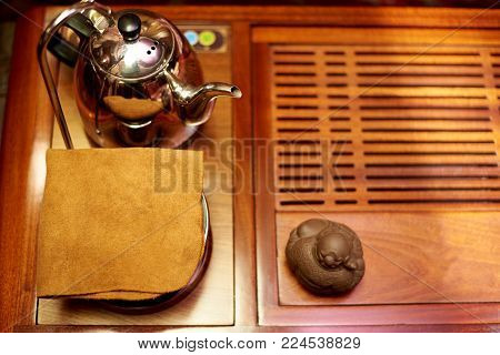 Preparation for the tea ceremony. Napkin, teapot, toy for tea ceremony on a wooden board. Copy space