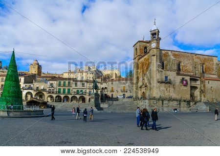 TRUJILLO, SPAIN - DECEMBER 30, 2017: Scene of Plaza Mayor, with San Martin church, a Christmas tree, locals and visitors, in Trujillo, Extremadura, Spain