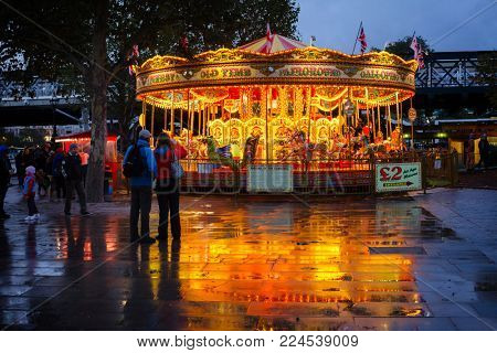 LONDON, UK - OCTOBER 27, 2012: Old-fashioned style Merry-Go-Round or carousel on the Queen's Walk promenade, the southern bank of the River Thames