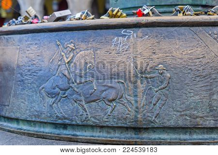 MADRID, SPAIN - DECEMBER 31, 2017: Lamp pole base in Plaza Mayor (main square), with carving and love locks, in Madrid, Spain