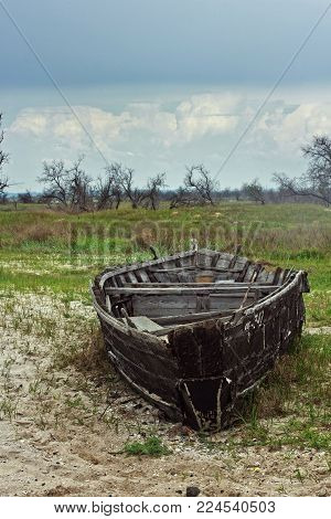 Broken rotten wooden boat on the seashore sand. Abandoned boat on the seashore or river. Boat wood rotted by time and weather. The ship is in the sand on a background of trees and shrubs. On the huge clouds of heaven. The sky is blue and beautiful.