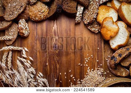 Assortment of baked bread on the background of a wooden table. seeds of wheat in a sieve and buckwheat seeds, spikelets of wheat and also oats and prunes. view from above. place for text
