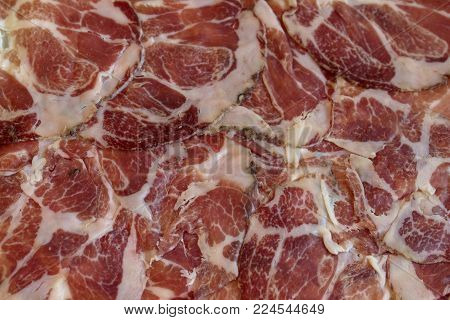 Texture of Italian delicacy dried meat in shades of red and white.