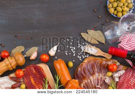 Meat appetizers - jamon, ham, chorizo, bacon with fresh olives, tomatoes, wine and spice on a dark wooden background .