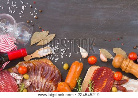 Cutting board with jamon, prosciutto, bacon, salami, chorizo and red wine on a dark wooden background. From top view.