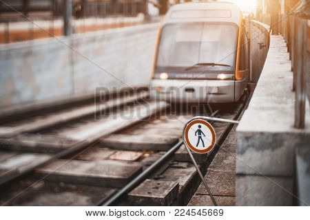Tilt-shift view of modern glossy subway train or city tram coming from underground tunnel into outdoor road section with railroad danger sign