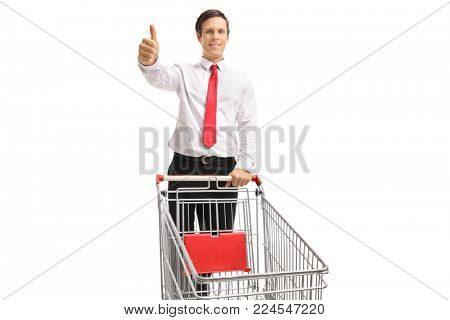 Formally dressed man with an empty shopping cart making a thumb up gesture isolated on white background