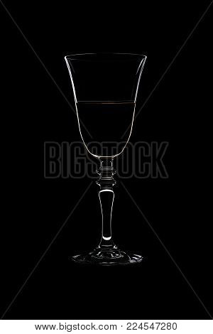 Glass with threaded on the stemwith a white wine isolated on black background.