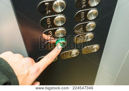 The man's hand presses the first floor button in the elevator