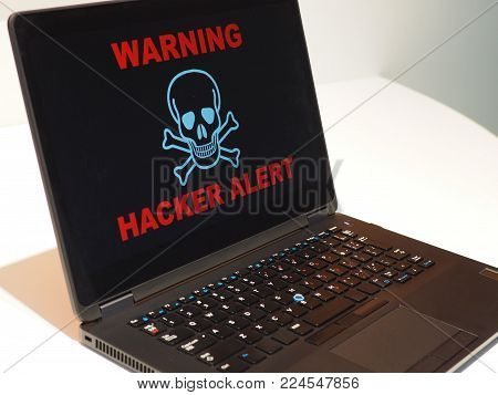 Hacker Alert concept. Generic laptop with large hacker alert warning across the screen.