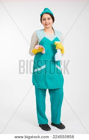 Full length photo of young brunette mais in uniform and yellow protective gloves spraying the cleaner on window, isolated on white background