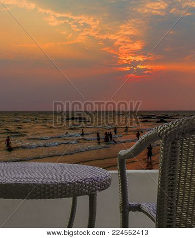rattan chair on balcony hotel room with outside sky and beach view