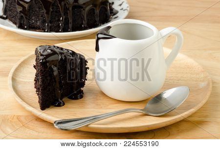 Piece of chocolate cake with chocolate sauce for pouring on top