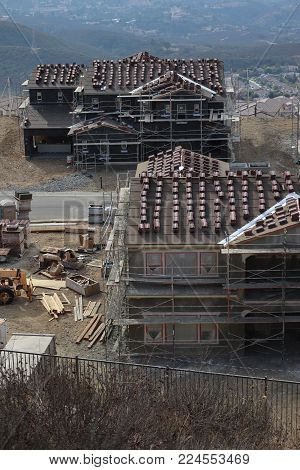 Several new houses under construction viewed from a hillside, clay tiles piled up on the roofs for installation, tar paper on siding, lumber stacked in area, dirt yards, scaffolding poster