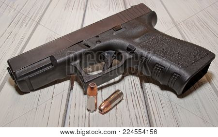 A black 9mm pistol with two hollow point bullets in front of it on a wooden table