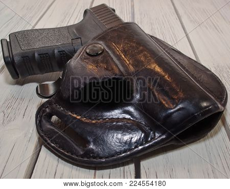 A black 9mm pistol shown in a holster laying on a wooden table