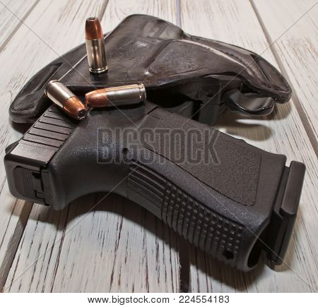 A black 9mm pistol in a holster on a wooden table, three hollow point bullets are on the top of the holster