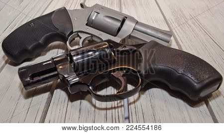 Two revolvers, a black 38 special and a stainless 44 spl together on a wooden table