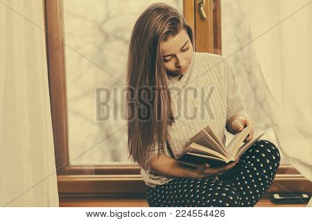 A nice girl is reading a book sitting on the windowsill. Pleasant pastime.