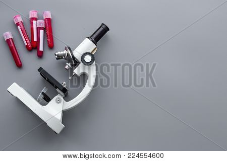 Do blood test in laboratory. Analysis. Blood samples in test tubes near microscope on grey background top view.