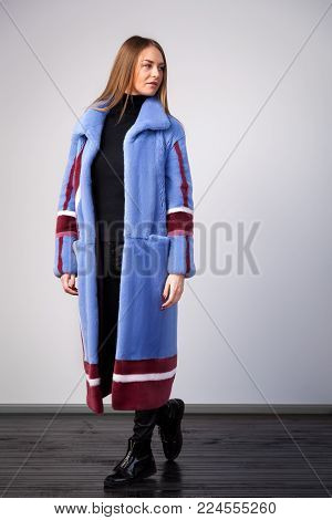 Young dark-haired woman in blue fur coat made from natural mink fur with claret-colored white stripes is relaxed, posing  on white isolated background