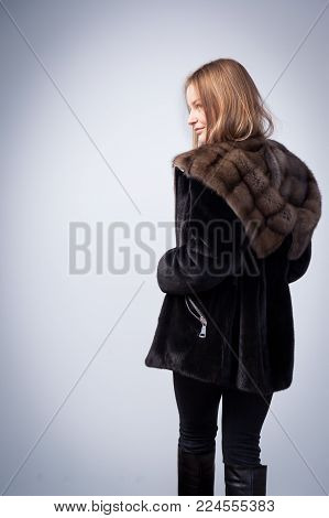 Young dark-haired woman in black fur coat from natural mink fur holds in her hand a black backpack and posing on white isolated background