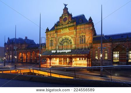GRONINGEN, NETHERLANDS -DECEMBER 31, 2016: People in front of the train station in evening. The current station building was designed by Izaak Gosschalk and completed in 1896