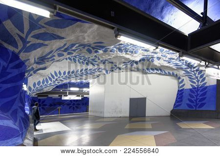 STOCKHOLM, SWEDEN - DECEMBER 26, 2016: People in a subway station. Over 90 subway stations have been decorated with sculptures, mosaics, paintings and reliefs by over 150 artists