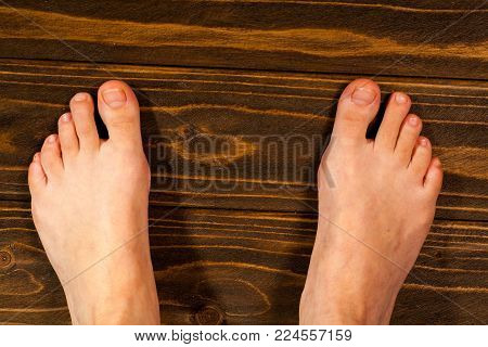 young girl steppe feet with itchy feet uses his big toe to scratch his other foot on wooden floor.