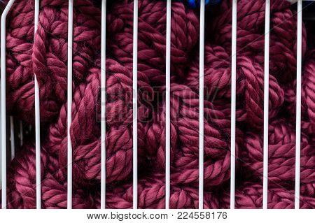 Balls of purple knitting yarn in white metal grid