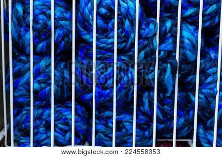 Balls of dark blue knitting yarn in white metal grid