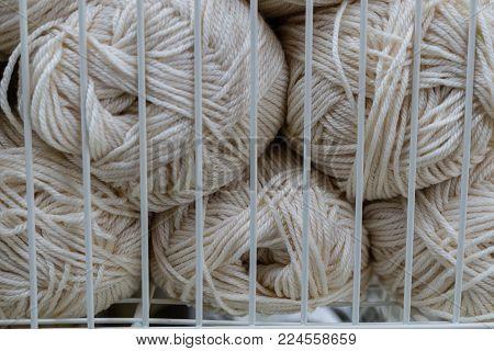 Balls of white knitting yarn in white metal grid