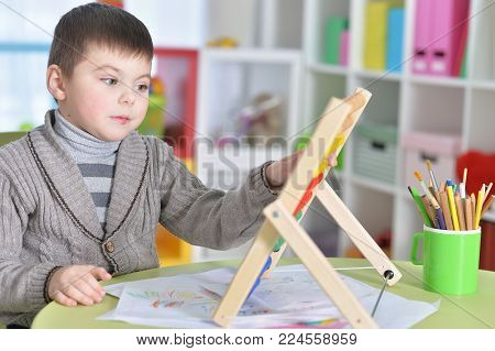 Little boy sitting at table and learning to use abacus