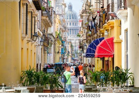 HAVANA,CUBA - JANUARY 27,2018 : Colorful street scene in Old Havana with the Capitol building on the background