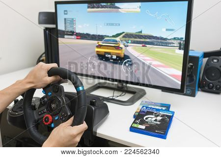 Melbourne, Australia - Jan 30, 2018: A man playing Gran Turismo Sport on PlayStation 4 Pro with steering wheel at home. GT Sport is a popular racing game developed by Polyphony Digital.
